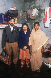 Family group standing in bedroom; with suitcases on a shelf and stains on the wall,