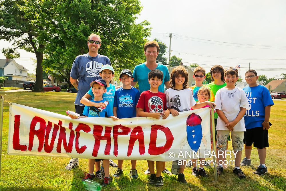 Seaford, New York, U.S. 20th July 2013. Legislator DAVE DENENBERG, at center, Nassau County LD. 19, and DENNIS FLEURY, at far left, Director of Tackapausha Museum and Preserve, and children gather outdoors at the Launchpad sign where water rockets are launched on Science Exploration Moon Day, presented by Long Island Fringe Festival 5. Despite the heat wave, the Tackkapausha hosted family event was very well attended.