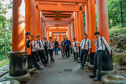 """Young men pose in suits at Fushimi Inari Taisha, an important Shinto shrine in southern Kyoto, Japan. Bright vermilion Senbon Torii (""""thousands of torii gates"""") straddle a network of trails behind its main buildings. The trails lead into the wooded forest of the sacred Mount Inari (233 meters). Fushimi Inari is the most important of several thousands of shrines dedicated to Inari, the Shinto god of rice. Foxes are thought to be Inari's messengers, honored in many statues. The shrine predates the capital's move to Kyoto in 794. The torii gates are donated by individuals and companies, as inscribed on the back of each gate. Prices for small to large gates run from 400,000 to over one million yen."""
