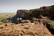 A group of tourists and their guide look at the sandy plain that follows the cliff in the Bandiagara Escarpment. The Dogon Country is the most visited part of Mali with tourists visiting its tipical  villages that can be located on the cliff, on the sandy plain or in the rocky plateau