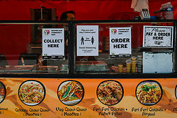 © Licensed to London News Pictures. 13/06/2020. WATFORD, UK. Signs on a street food seller's stall in Watford High Street.  To try to stimulate the economy, the UK Government is easing coronavirus pandemic lockdown restrictions to permit non-essential shops to re-open on 15 June, but only if they are Covid19 compliant.  Shoppers will also need to practice social distancing.  After a record 20.4% reduction in gross domestic product (GDP) in April, the country is on course for the worst recession in more than three centuries.  Photo credit: Stephen Chung/LNP