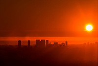 Century City in silhouette with sunset over the Pacific Ocean behind, Los Angeles, California USA.