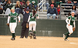 30 March 2013:  Home plate umpire calls the batter out after Katie Crane pulls in a popped up ball in front of Chloe Montgomery and Emma Clark during an NCAA Division III women's softball game between the DePauw Tigers and the Illinois Wesleyan Titans in Bloomington IL<br /> <br /> Umpire is Jay MacDaniels of Pekin IL