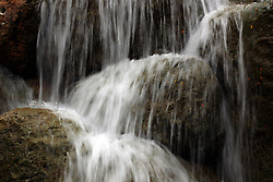Water falls down over rocks in a small manmade waterfall that is part of a miniature golf course.