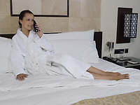 beautiful calm and serene woman in palace hotel room lying on a king size bed phonig