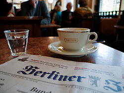 Detail of Berlin newspaper and cup of coffee at famous Cafe Einstein on Unter Den Linden in Berlin