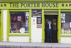 Main in business suit talking on cell phone outside The Porter House pub, Westport, County Mayo, Ireland