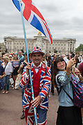 On the 100th anniversary of the Royal Air Force RAF and following a flypast of 100 aircraft formations representing Britains air defence history which flew over central London, a patriotic man wearing a Union Jack suit and carrying a flag walks down the Mall, on 10th July 2018, in London, England.