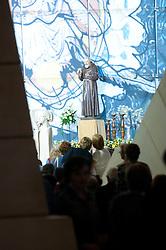 """È stata inaugurata il 1° luglio 2004, la nuova Chiesa di San Pio da Pietrelcina progettata dall'architetto Renzo Piano. Esattamente 45 anni prima, nel 1959,  veniva inaugurata la chiesa """"grande"""" di Santa Maria delle Grazie. .Sorta a fianco del santuario e convento in cui visse il frate, ha la forma di una conchiglia e la sua pianta ricorda quella della spriale archimedea. Enormi archi parto dal perimetro esterno e terminano nel fulcro della """"conchiglia"""" dove è posto l'altare. Possenti staffe d'acciaio, ancorate agli archi, sorreggono la volta che ricoperta di rame preossidato espone alla vista un intenso un colore verde-rame.   .Con i suoi 6000 mq, è la seconda chiesa più grande in Italia per dimensioni, dopo il Duomo di Milano. Può ospitare oltre 7000 persone e per la sua realizzazione sono state impiegati 30.000 metri cubi di calcestruzzo, 1.320 blocchi in pietra di Apricena, 70.000 metri cubi di scavo in roccia, 60.000 chili di acciaio, 500 mq di vetro, 19.500 mq di rame preossidato. Ogni anno è meta di oltre sei milioni di pellegrini..Nella foto, scorcio dell'interno della chiesa con sullo sfondo la statua di padre Pio circondata da fedeli in preghiera."""