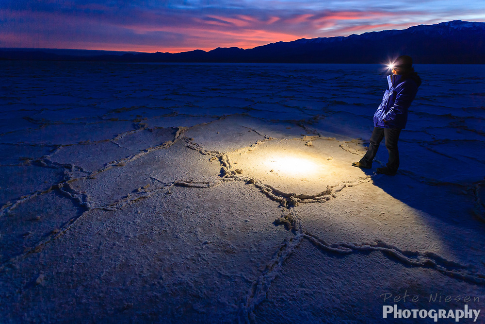 Hiker with headlamp crosses desert salt flats at night in Death Valley National Park