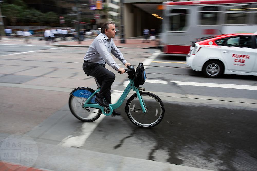 Een man rijdt op een fiets van Bay Area Bike Share, het deelfietssysteem in San Francisco. Het openbaar huursysteem is vanaf 2013 operatief in San Francisco en bestaat momenteel uit ongeveer 700 fietsen verdeeld over 70 geautomatiseerde stations. De fietsen kunnen bij elk station worden gepakt en op een willekeurig ander station worden neergezet. Per rit is het eerste half uur gratis, de huurfietsen zijn bedoeld voor korte ritten.<br /> <br /> A man rides a bike of the Bay Area Bike Share, the bike sharing system in San Francisco. The public rental system has been operative since 2013 in San Francisco and currently consists of about 700 bikes spread over 70 automated stations. The bikes can be picked up at each station and put down at any other station. Per trip, the first half hour is for free. The rental bicycles are provided for short journeys.