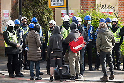 © Licensed to London News Pictures. 29/03/2021. London, UK. A group of evicted squatters gather as police and bailiffs surround the former Cavendish Road Police Station in Clapham in south London, where squatters had occupied the building as part of a 'Kill The Bill' protest. Murdered woman Sarah Everard walked past the building on the night she went missing on March 3, 2021. Photo credit: Ben Cawthra/LNP