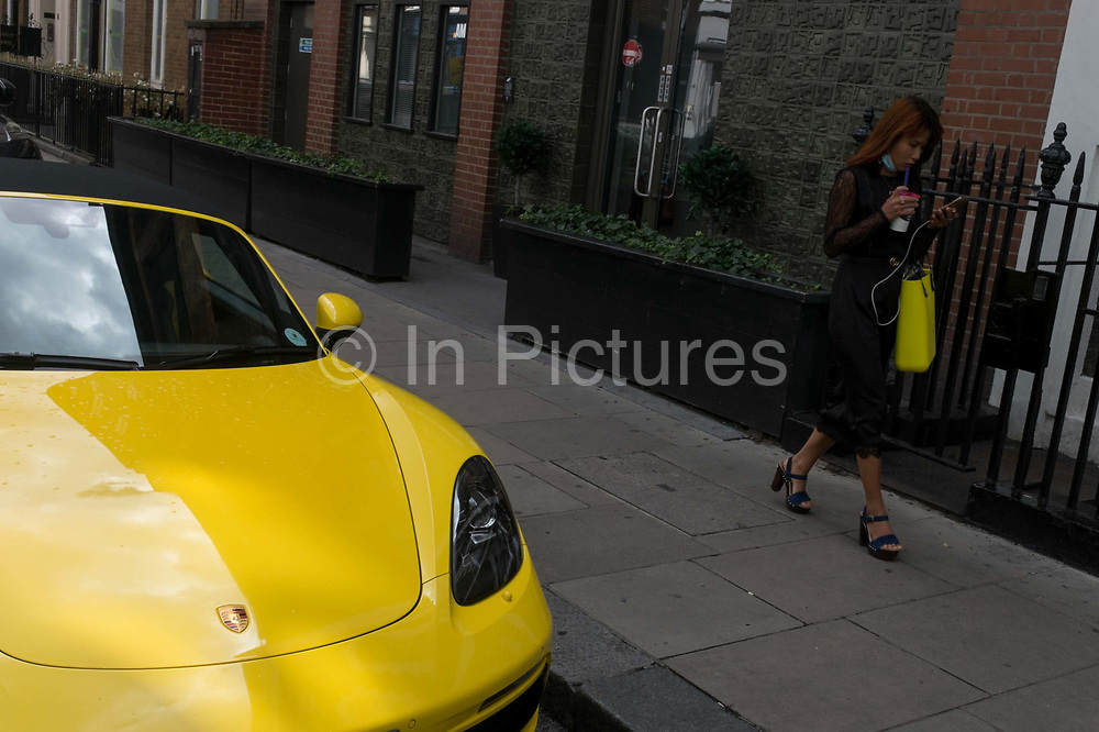 A young woman carrying a yellow handbag and looking at her phone, walks past a matching yellow Porsche sports car in Londons Soho, the West End, on 2nd July 2020, in London, England.