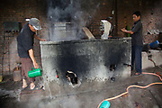 Wool is being washed at high temperatures, the fire is fueled by kerosene.<br /> Amity Factory does not employ children and is a licensee of the GoodWeave Foundation and their carpets carry the GWF label.The weavers work according to the design,printed on paper hanging above them. Most are women and many mothers and they work inthe factory 12-14 hours /day 6 days/week. The Good Weave Foundation is a charity set up in partnership with the Nepalese carpet industry. The aim is to eliminate child labor in all carpet factories in Nepal. Factories which do not employ children can sign up with the charity and become a licensee to the GWF brand and label their carpets with the GWF label which promises any buyers abroad that no children were involved in making the carpets.