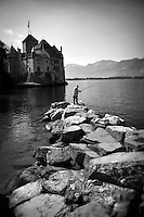 Black and white photo of a man standing on large rocks and fishing in Lake Geneva outside of the Chateau de Chillon in Montreux, Switzerland.