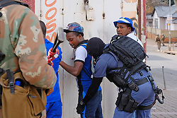 JOHANNESBURG, SOUTH AFRICA - APRIL 18: Men are searched by a SAPS officer during a South African Police Service (SAPS) Metro Police and Army supported patrol in Rockey Street, Yeoville. Random searchs and social distancing measures on April 18, 2020 in Johannesburg South Africa. Under pressure from a global pandemic. President Ramaphosa declared a 21 day national lockdown extended by another two weeks, mobilising goverment structures accross the nation to combat the rapidly spreading COVID-19 virus - the lockdown requires businesses to close and the public to stay at home during this period, unless part of approved essential services. (Photo by Dino Lloyd)
