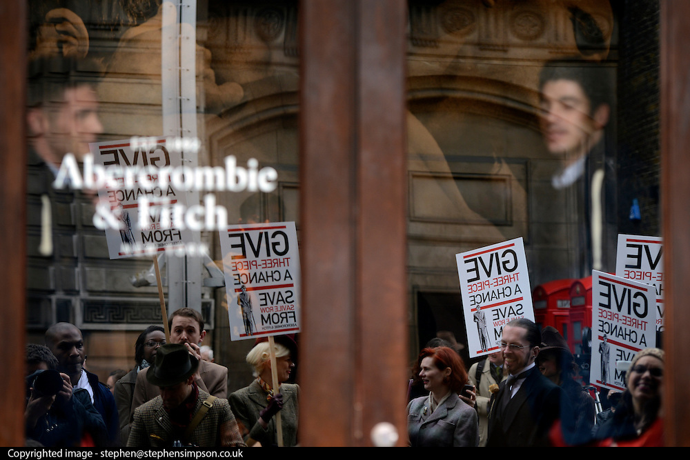 © Licensed to London News Pictures. 23/04/2012. London, UK . A Abercrombie staff member watches the protest reflected in the current store entrance. A protest organised today, 23rd April 2012, by Chap Magazine and the Tailors of Savile Row to petition against the proposed opening of a new Abercrombie and Fitch Store on Savile Row. The protesters gathered to sing 'Give 3 Piece A Chance' outside the present store on Burlington Gardens. Photo credit : Stephen Simpson/LNP