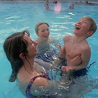 A mother and her sons play in an outdoor swimming pool at Montana's Big Sky resort.