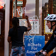 A protester paints on a business's window while Black Lives Matter protesters march towards the capitol after gathering at Lafayette park to defy the curfew and protest the killing of George Floyd in Minneapolis.