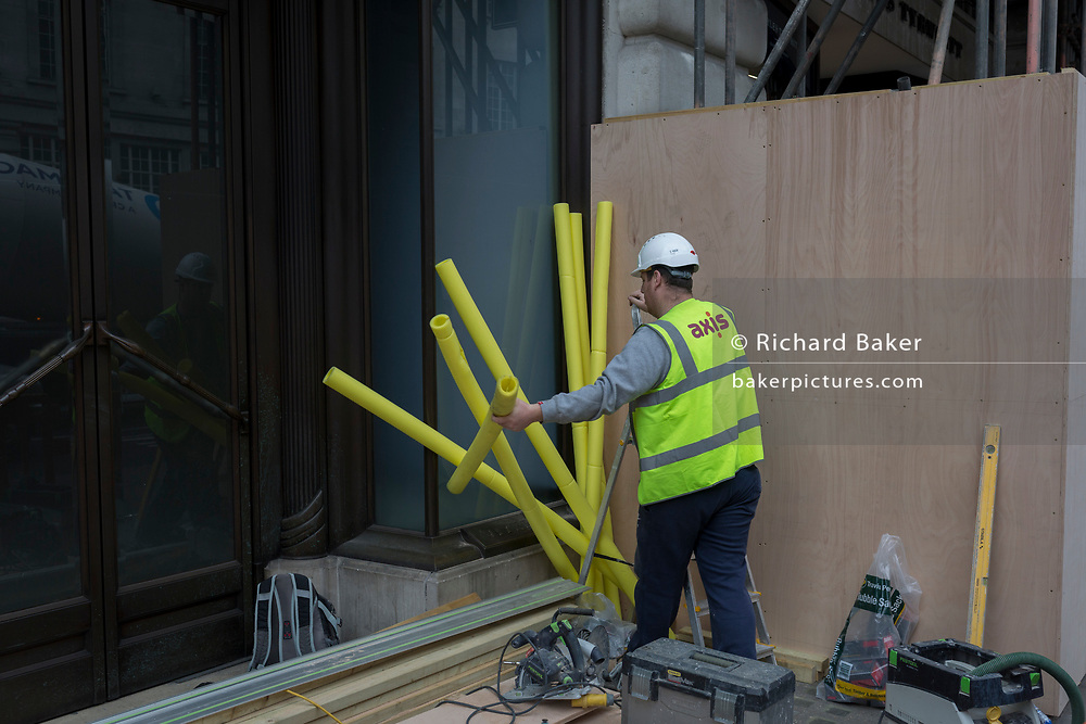 A workman struggles with a number of yellow foam scaffolding protection sleeves, on 4th May 2017, in London, England.