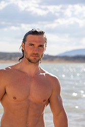 good looking shirtless man in a lake