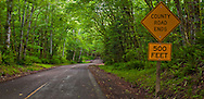 "A rural country Kitsap County road with a ""County Road Ends"" sign in a Big Leaf Maple and Red Alder deciduous forest on the Kitsap Peninsula in Puget Sound, Washington state, USA."