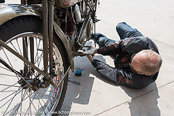 Harry Verkuil of Scotland changing the oil in his 1916 Model F class-3 Harley-Davidson at a gas stop during the Motorcycle Cannonball Race of the Century. Stage-6 from Cape Girardeau, MO to Springfield, MO. USA. Thursday September 15, 2016. Photography ©2016 Michael Lichter.