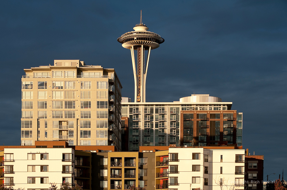 The Space Needle (center) rises behind residential buildings at sunset, Seattle, Washington