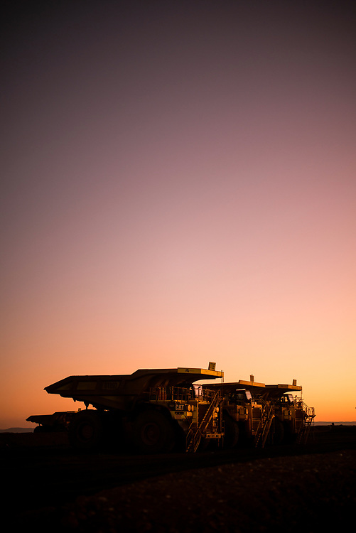 "Haulage trucks wait on the ""go-line"" at a mine site in the Pilbara region of Western Australia."
