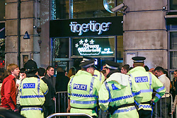 © Licensed to London News Pictures . 01/01/2014 . Manchester , UK . Police outside Tiger Tiger at Manchester's Printworks club venue . Revellers see in the New Year in Manchester today (January 1st 2014) as police report that officers are at full stretch responding to calls . Photo credit : Joel Goodman/LNP
