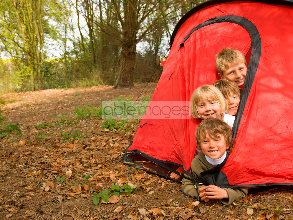 Portrait of a group of children coming out of tent opening