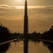 The early morning sun silhouettes the Washington Monument on the Reflecting Pool in Washington DC. Scaffolding surrounds the Monument part of the way up.