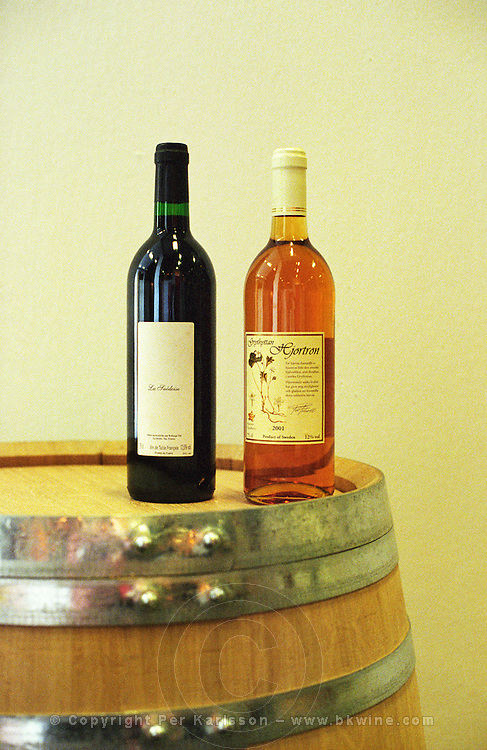 A wine barrel made from Swedish oak by a cooper in Sweden with two bottles of wine that has been aged in such barrels: one French table wine called La Suedoise (the Swedish woman or simply the Swede, in feminine form) made by Domaine Rabiega in Provence and a bottle of Grythyttan fruit berry wine made from cloudberry cloudberries rubus chamaemorus