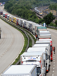 © Licensed to London News Pictures. 28/07/2015<br /> Operation stack lorries between J8 and J9 for Ashford on the M20. Eurostar train in picture (r)<br /> Operation stack is back on the M20 in Kent.<br /> Just days after Operation Stack was taken off the M20, it was brought back in the early hours of this morning.<br /> The authorities are blaming a heavy volume of traffic heading towards the Port of Dover and Eurotunnel and the continued disruption in Calais.<br /> The coast-bound carriageway between junctions 8 and 9 is closed to allow lorries to park, but the slip roads at junctions 9, 10 and 12 and 13 have also been shut. <br /> <br /> (Byline:Grant Falvey/LNP)