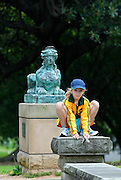 Child (10 years old) crouched before one of the two sphinxes on either side of the pathway opposite and facing the Art Gallery of New South Wales. The sphinxes are bronze casts of two original sandstone sphinxes from the estate of Sir James Martin. They resided near the swings on the eastern side of Art Gallery Road for many years. The Domain, Sydney, Australia