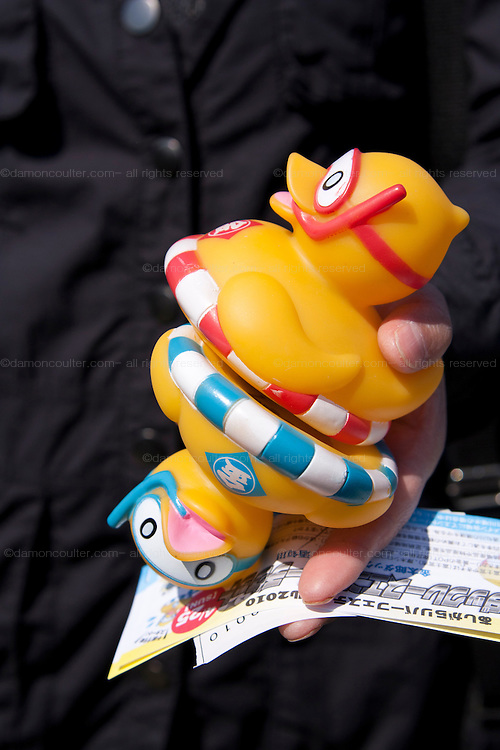 A woman holds two rubber ducks and tickets for the prize giving after The Ashigara River festival, Kintaro duck-race in Matsuda, Kanagawa, Japan April 25th 2010