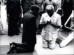 Feb. 26, 2012 - Historic moment in African history. After an absence of more than ten years from Uganda soil, Zambia President Kenneth Kaunda, reunited with reinstated President Milton Obote, kneels in prayerful thanksgiving at Entebe Airport, Uganda. President Kaunda was taking part in a four nation heads of state summit with the Presidents of Kenya and Tanzania. (Credit Image: © Keystone Pictures USA/ZUMAPRESS.com)