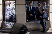 Models on a poster of a stylish clothing shop for businessmen are reflected in the bonnet of a black vehicle parked in the City of London. A businessman stops with a cigarette to check his messages alongside very good-looking and stylish men wearing sharp suits - the latest in 2015 city fashion.