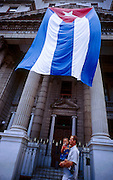 25 JULY 2002 - HAVANA, HAVANA, CUBA: A man carries his son past a Cuban flag hanging from the Ministry of Prices and Finances building in the historic section of Havana, Cuba, July 25, 2002..PHOTO BY JACK KURTZ