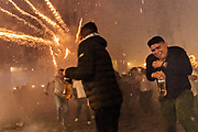 Mexican men carrying bottles of tequila scramble as they are pelted by pyrotechnic rockets during the Alborada festival September 29, 2018 in San Miguel de Allende, Mexico. The unusual festival celebrates the cities patron saint with a two hour-long firework battle at 4am representing the struggle between Saint Michael and Lucifer.