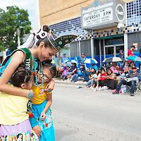 Angeline Platero, 15, the 2019-2020 Thoreau Veterans Princess is hugged by sisters Leila Laner, 6, right, and Carter Laner, 4, at the Gallup Inter-Tribal Indian Ceremonial parade Saturday morning in downtown Gallup.