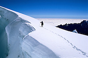 Paul Vance mountaineering along a gaping crevasse during an ascent of 19,970 ft. Nevado Huayna Potosi in the Cordillera Real Range, Bolivian Andes. The cloudy Amazon Basin is in the distance.