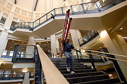 Randy Cook, a cable technician with AFL Network services, carries a ladder down one of the two staircases that sore through the atrium of the new UNC Charlotte Student Union.  L.MUELLER/Charlotte Observer