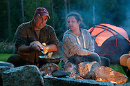 Angra, Hälsingland, Central Sweden, August 2013. Marco, Sonja and Luna Hassoldt cooking on an open fire at the campsite. Camp Angra is a wilderness camping near Karbole owned by the Dutch Hassoldt family. Marco specialises as a wilderness guide and the camping offers Fishing and Flyfishing, Wildlifewatching, birding, outdoor fun, hiking, biking and canoeing, while Sonja runs the camping. The extensive forests dotted with hundreds of lakes of a spectacular landscape for wilderness camping. hike through the forests picking berries and collecting mushrooms, see moose and track bears and wolves. Navigate the lakes in a canoe and catch trout and pike with a fly rod and see beavers.  Gavleborg and Dalarna regions are bursting with adventure. Photo by Frits Meyst/Adventure4ever.com