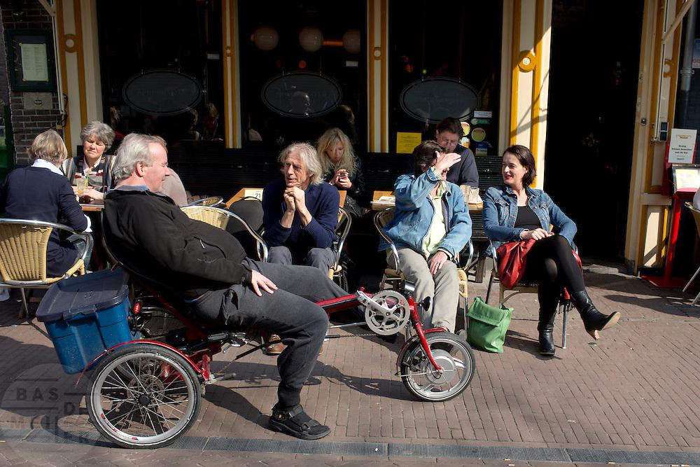 Een man op een ligfiets schuift even aan bij het terras bij Springhaver.<br /> <br /> A man on a recumbent bike is talking at a terrace in Utrecht.