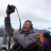 World Heli Challenge event organiser Tony Harrington taking photographs at the end of the days competition during the World Heli Challenge Extreme Day at Mount Albert on Minaret Station, Wanaka, New Zealand. 1st August 2011