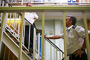 Two prison officers talking on a landing in one of the residential wings at HMP Wandsworth. HM Prison Wandsworth is a Category B men's prison at Wandsworth in the London Borough of Wandsworth, South West London, United Kingdom. It is operated by Her Majesty's Prison Service and is one of the largest prisons in the UK with a population over 1500 people. (photo by Andy Aitchison)