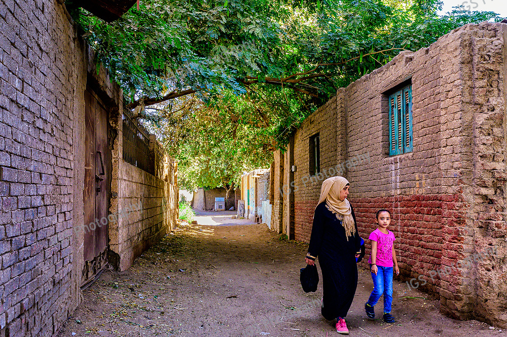 Mother and daughter walking through the village streets on Geziret Al Dahab Island