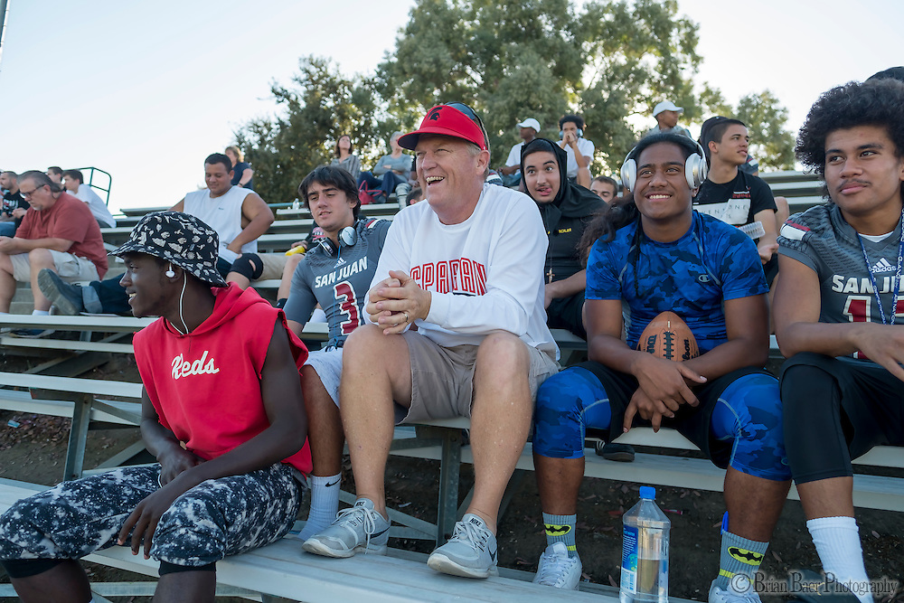 San Juan Spartans head coach Greg Roeszler sits with his varsity team in stands as they watch and cheer for the JV game as they host the Mira Loma Matadors, Friday Sep 16, 2016.<br /> photo by Brian Baer