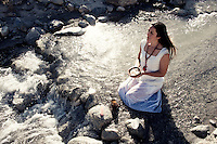 Find this pure heart inside yourself and be your wild flowing being.<br /> <br /> . Spiritual woman meditating with joy and fullness in the flow of a wild river. She is intentionally in free ritual holding an alms bowl with it's wild water and Quartz receiving good vibrations and high frequency connection.